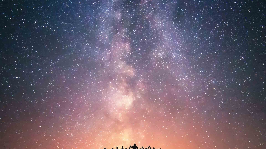 Photo of a starry sky with silhouettes of people