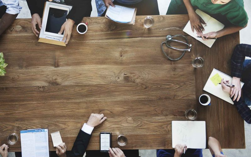 Photo of a doctors discussing at a wooden table