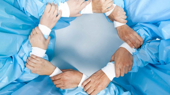 Photo of hands of surgeons forming a circle