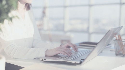 Female blogger typing on a laptop