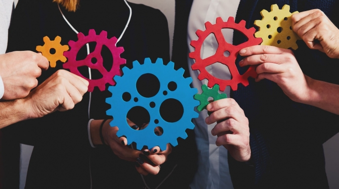 Teamwork of businesspeople work together and combine pieces of gears. Partnership and integration concept
